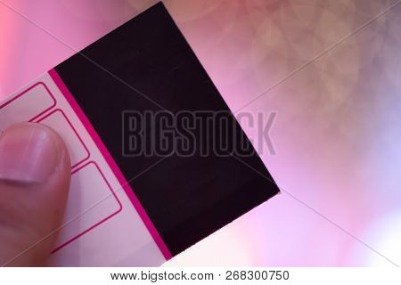 Hand Holding Ticket For Special Event With Pink Lighting Background