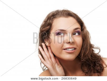 Young beautiful woman cups her hand to hear better, over white background