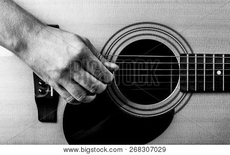 Old Mans Hand On The Strings Of An Acoustic Guitar. Close-up.