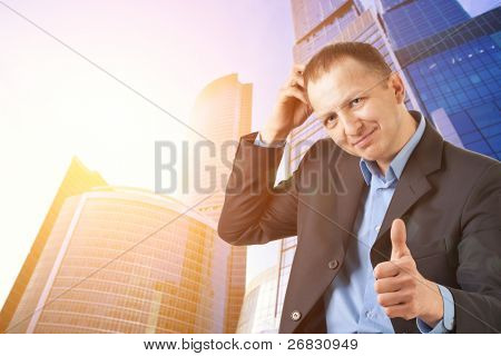 Businessman showing thumbs up sign against the office building