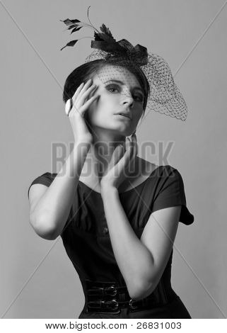 Studio portrait of a beautiful retro styled woman with professional make-up wearing vintage hat  (black and white)