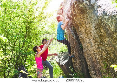 Climbing In Nature. Friends Climb To The Stone. The Girl Climbs On The Stone, And Friends Support He
