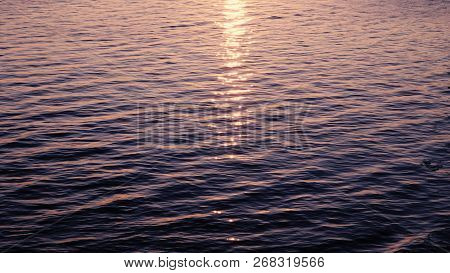 Sun Glistens In The Water, The Pink Sunset Is Reflected In The Waves