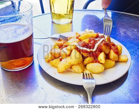 A Portion Of Patatas Bravas Over A Metallic Table. Fried Potatoes Topped With Spicy Sauce, Also Know