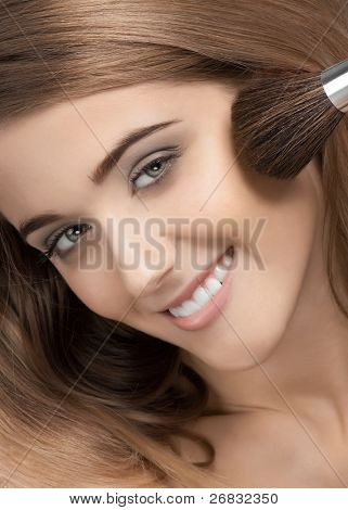 Close-up portrait of pretty young woman applying makeup, isolated on white