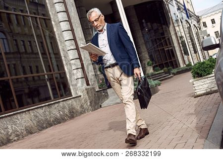 Reading The Latest News. Confident Senior Man In Casual Suit Reading Newspaper While Standing Outdoo