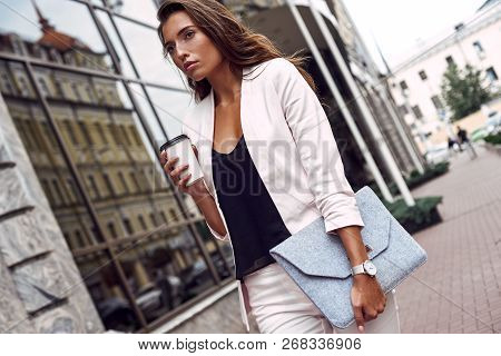 Enjoying Her Coffee Break. Attractive Young Woman Holding Disposable Cup And Clutch While Walking Ou