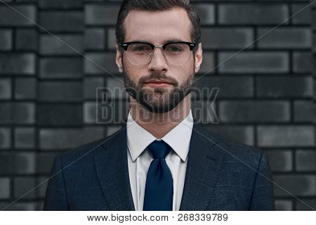 A Confident View Of The Leader. A Young Businessman In Glasses And With A Beard Looks Directly At Yo