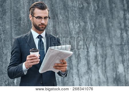 Young Businessman In Suit And Glasses Holding A Paper Cup And Reading Business Newspaper In His Hand