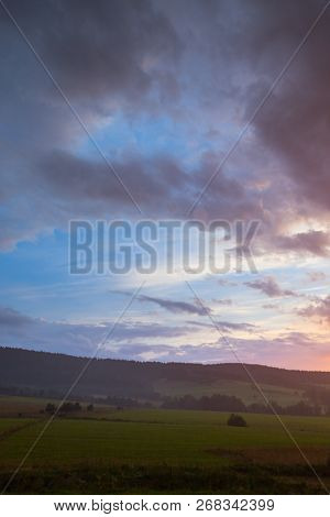 Beautiful Sunset Sky. Landscape With Cloudy Sky, Trees, Meadow And Hill