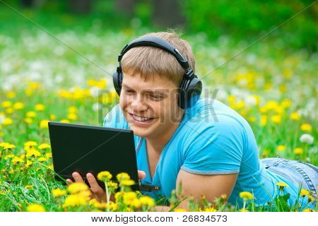 Happy young man working with a laptop and listening music on headphone outdoors