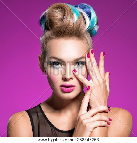 Beautiful woman with fashion hairstyle and pink nails.  Fashion portrait of young caucasian model with bright makeup.  Fashion makeup.  Closeup portrait. Gorgeous face of an attractive girl - studio.