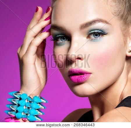 Closeup portrait of a beautiful fashion woman with bright makeup.  Gorgeous glamour girl of an attractive stylish girl - pink background. Portrait of a girl with bracelets  thorns. Jewelry. Glamour.