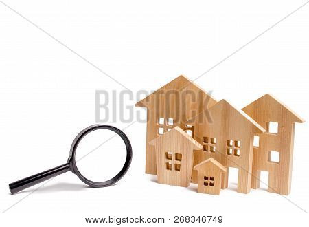 Wooden Houses And Magnifying Glass On A White Isolated Background. Home Search Concept. Affordable H