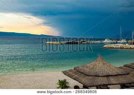Beautiful View Of Sandy Beach With Straw Umbrellas, Port And Small Lighthouse On Stone Pier In Front
