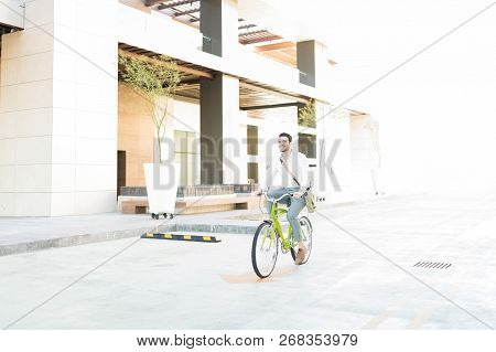 Efficient Young Businessman Commuting On Bicycle In City