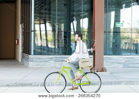 Male Environmentalist In Formal Commuting By Bike Against Modern Office