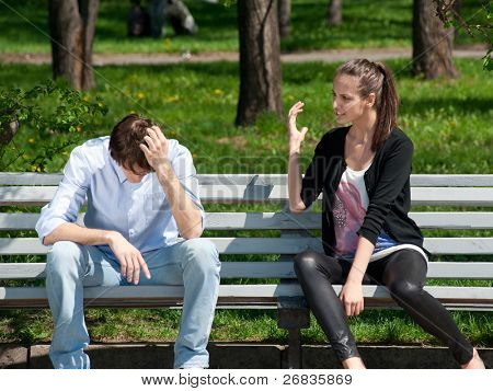 Young couple in quarrel sitting on bench in park