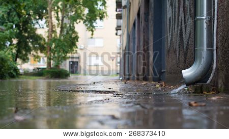 Downpipe Is Discharging Water Over A Downpipe Shoe Straight Into A Flooded Street. A Few Raindrops A