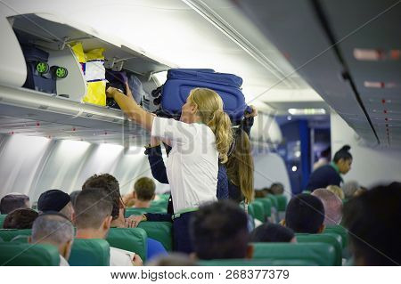 The Stewardess Helps The Passengers To Put Their Luggage In The Cabin Of The Plane. Stewardess In Th