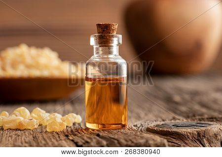 A Bottle Of Essential Oil With Frankincense Resin Crystals On A Table