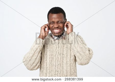 Portrait Of Furious Afroamerican Man Covering His Ears