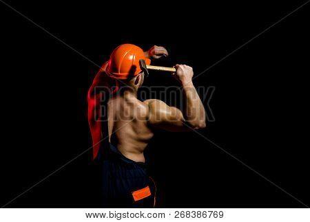 Already Under Construction. Construction Worker Hammer A Nail. Muscular Man Builder At Work Under Co