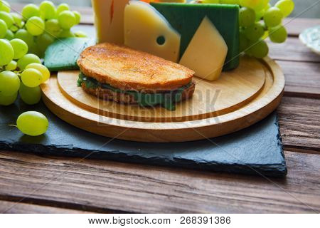 Hot Grilled Or Fried Sandwich With Green Cheese And Green Grapes On Black Slate Cheeseboard On Woode