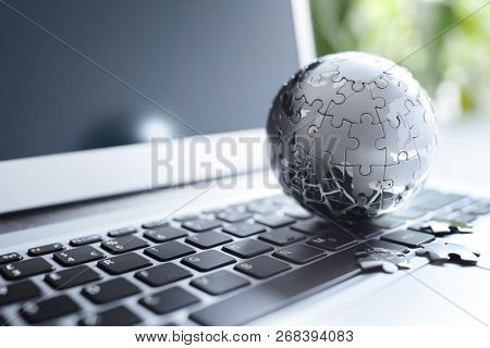 Global strategy solution concept - chrome earth jigsaw puzzle on laptop keyboard