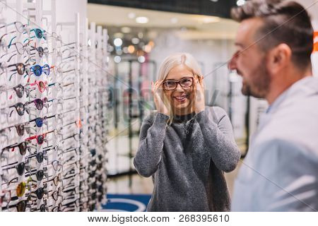 Optician and client choosing glasses together. Optical store, professional consulting.