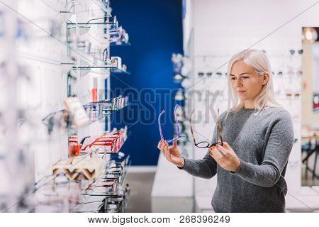 Woman comparing glasses at optic store. Eyewear shopping, correction glasses.