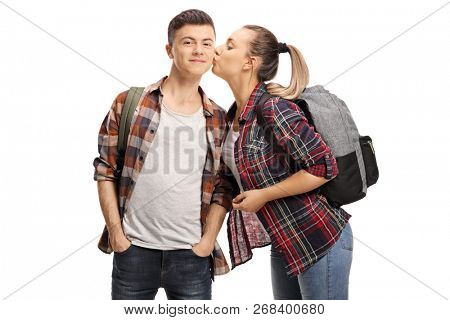 Teenage girl kissing a teenage boy isolated on white background