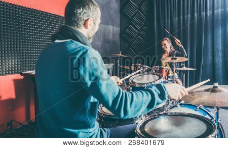 Woman receiving drum lessons from her music teacher in school