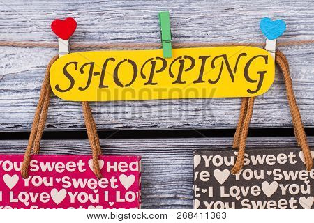 Yellow Paper Card With Inscription Shopping. Printed Shopping Bags On Grey Wooden Background. Valent