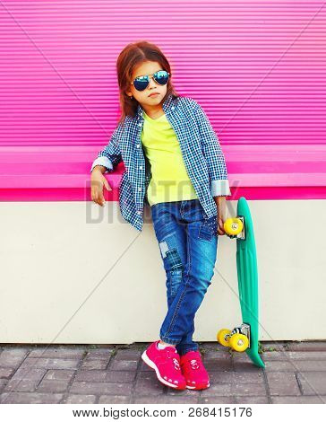 Fashion Child Little Girl With Skateboard On Pink Wall Background