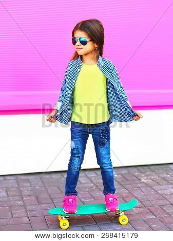 Fashion Little Girl Child On Skateboard In City On Colorful Pink Wall Background