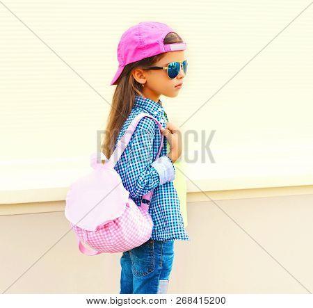 Fashion Little Girl Child Wearing Sunglasses, Baseball Cap, Backpack In Profile On White Background