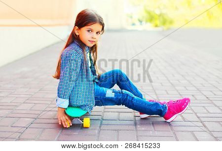 Fashion Little Girl Sitting On Skateboard On City Street