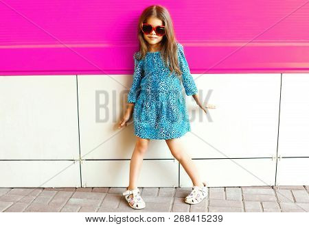 Fashion Little Girl Posing In Leopard Print Dress On Colorful Pink Wall Background