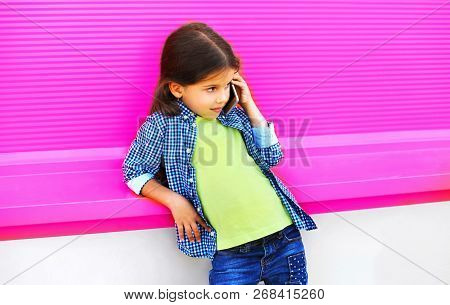 Little Girl Child Calling On Smartphone On City Street On Colorful Pink Wall Background