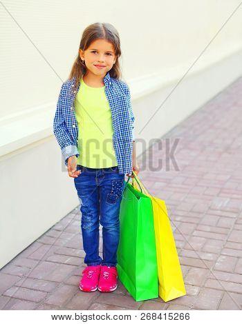 Little Girl Child Holds Shopping Bags On City Street