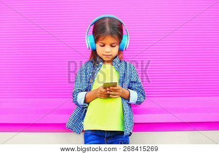 Little Girl Child With Smartphone Listens To Music In Wireless Headphones On Colorful Pink Wall Back