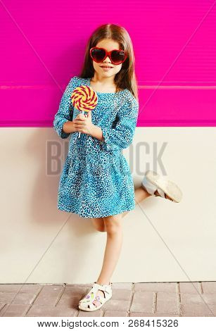 Portrait Little Girl Child With Lollipop Stick In Blue Leopard Dress On Colorful Pink Wall Backgroun
