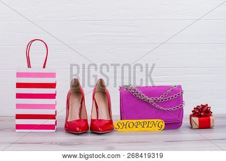 Fashion Female Accessories And Gifts. Shopping Background With Gift Bag, Red Stilettos, Pink Handbag