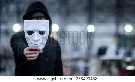 Mystery Hoodie Man With Black Mask Holding White Mask In His Hand. Anonymous Social Masking Or Bipol