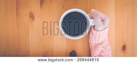 Woman Hand In Warm Pink Sweater Holding A Cup Of Coffee.