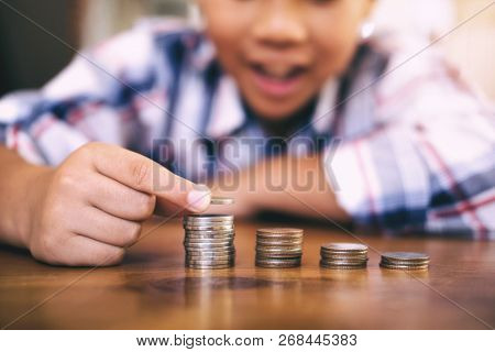 Saving Money Concept. Kid Counting Money And Make Coin Stack.