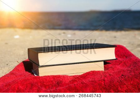 Books on beach with red towel and blue sky