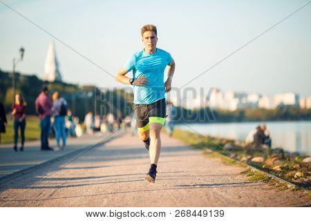 Photo of running athlete man at promenade on summer