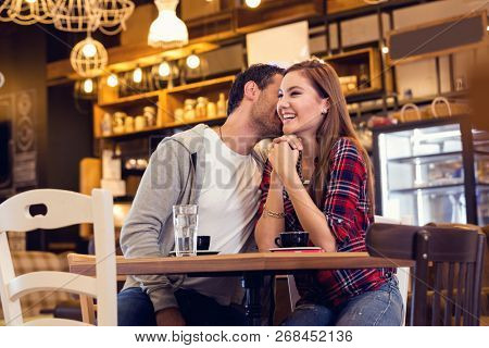 Young couple sitting in cafe and flirting